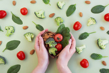 Healthy Food For Heart On Green Background. Womans Hands Hold Plate With Vegetables, Spinach And Nuts. Diet, Superfood And Health Concept. Top View, Flat Lay