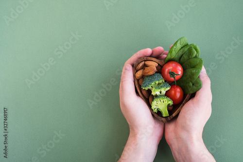 Fototapeta Healthy food for heart on green background. Man hands hold plate with vegetables, spinach and nuts. Diet, superfood and health concept. Top view, flat lay, copy space obraz