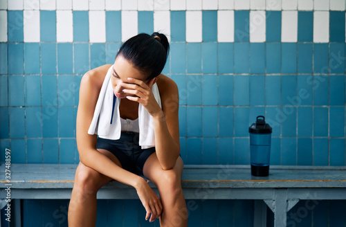 obraz PCV Tired fit woman with a towel in the locker room after hard workou