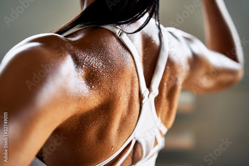 Close up of woman back with flexing her muscles