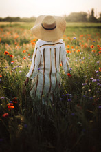 Young Woman In Rustic Linen Dress Walking Among Poppy And Cornflowers In Summer Meadow Countryside In Sunset Light. Rural Slow Life. Enjoying Simple Life. Girl In Hat In Wildflowers