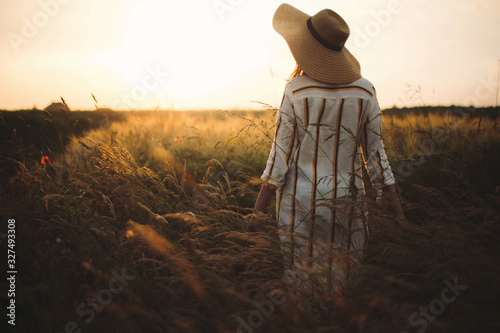 Woman in linen dress and hat walking in wildflowers and herbs in sunset golden light in summer meadow Canvas Print