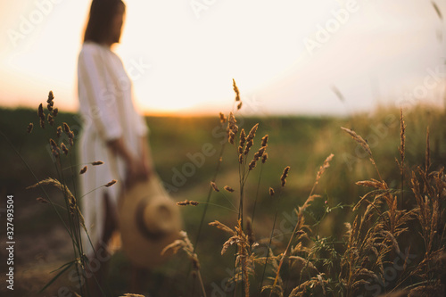 Fototapeta Herbs and grasses in sunset light on background of blurred woman in summer meadow. Wildflowers close up in warm light and rustic girl relaxing in evening in countryside. Tranquil moment obraz