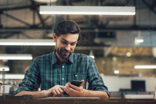 Happy young man with modern smartphone in hands stock photo