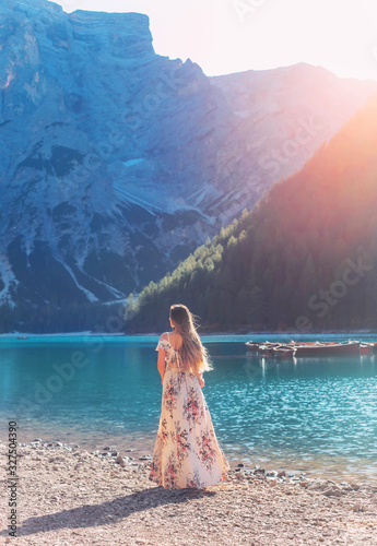 Obraz Girl with hair flying in wind red-haired, long silk elegancy dress floral print turned away stands on shore Lake Bryce enjoy silence beauty sunshine mountains. Backdrop boat water mountain with forest - fototapety do salonu