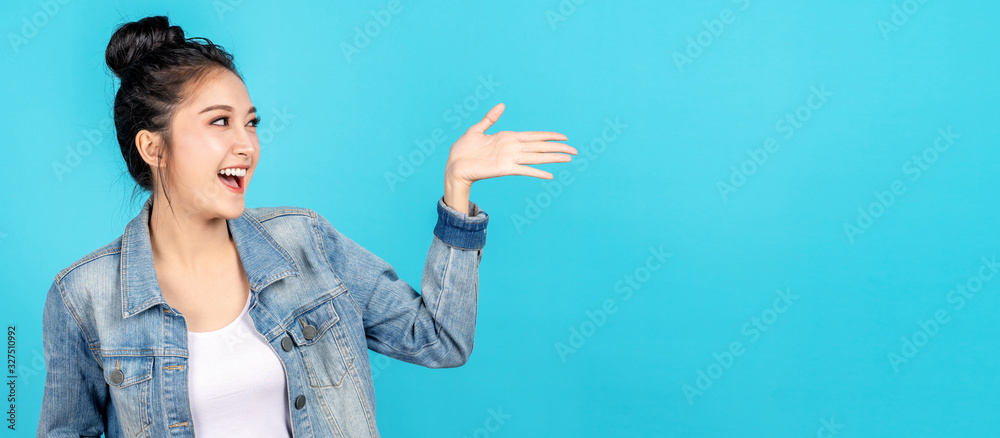 Fototapeta Banner of Happy asian woman feeling happiness and gesture hand open on blue background. Cute asia girl smiling wearing casual jeans shirt and present on copy space.
