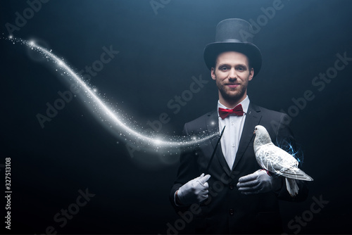 happy magician in hat making abracadabra with dove and wand in dark room with sm Wallpaper Mural