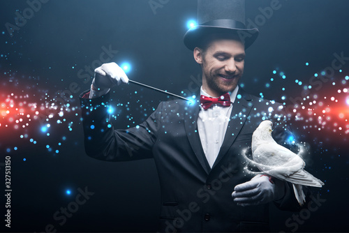 Photo happy magician in hat making abracadabra with dove and wand in dark room with sm