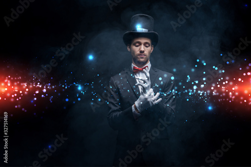 Fototapeta magician in suit and hat wearing gloves in dark smoky room with glowing illustra