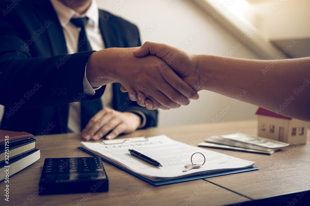 Fototapeta Home sales agents and buyers work on signing new homes and shaking hands.