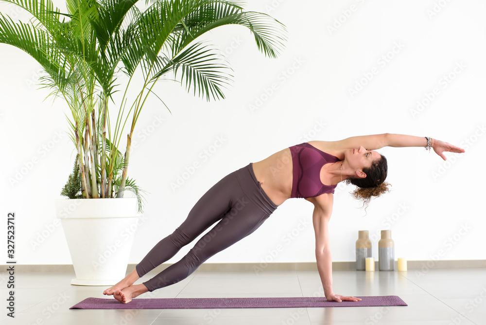 Fototapeta Woman doing side plank pose in yoga