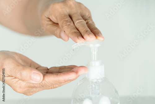 Senior hand apply alcohol gel or anti bacteria soap to make cleaning and clear v Wallpaper Mural