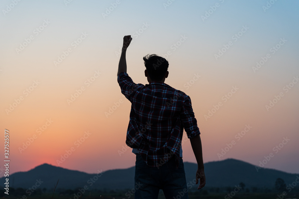 Fototapeta Man with fist in the air during sunset sunrise mountain in background. Stand strong. Feeling motivated, freedom, strength and courage concept.