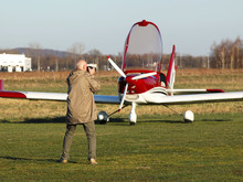 Yaslo, Poland - 7 9 2019: A Man Is Photographing A Red Sports And Tourist Red Turboprop Airplane Standing At A Grass Airfield. Free Time At An Air Show. Private Aviation For Travel And Entertainment
