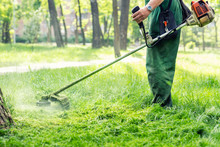 Worker Mowing Tall Grass With ...