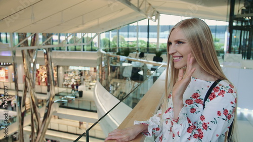 Photo Cheerful woman greeting acquaintance in mall