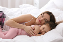 Happy Mother And Little Daughter Sleeping In Bed At Home
