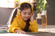 canvas print picture - Cute little girl with headphones and tablet listening to audiobook at home