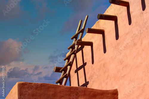 Photo An old wood ladder leaning on a red adobe wall under blue skies