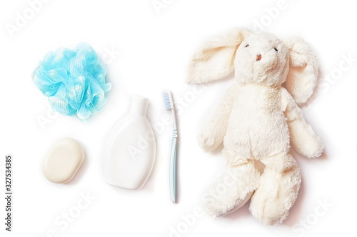 Flat lay baby care cosmetic products isolated on a white background. Blue sponge, soap bar, toothbrush and toy rabbit