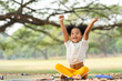 canvas print picture - Happy African american little girl smiling and raises her hand while sitting in the park