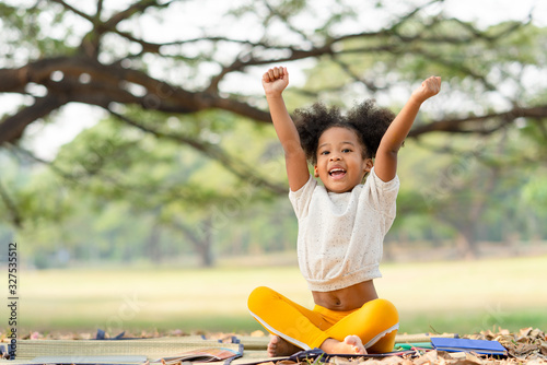 Obraz Happy African american little girl smiling and raises her hand while sitting in the park - fototapety do salonu
