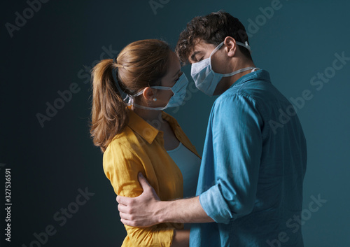 Fototapeta Young loving couple wearing face masks