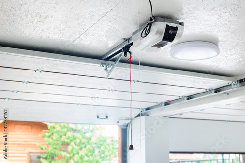 Fototapeta Opening door and automatic garage door opener electric engine gear mounted on ceiling with emergency cord