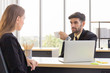 A male businessman holds a cup of coffee with the female secretary in the office in a serious manner