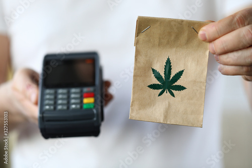 Obraz Package delivery with marijuana, payment terminal. Use and storage medical marijuana. Legalized narcotic herb. Treating pain, stress and insomnia. Registered medical hemp delivery agent - fototapety do salonu