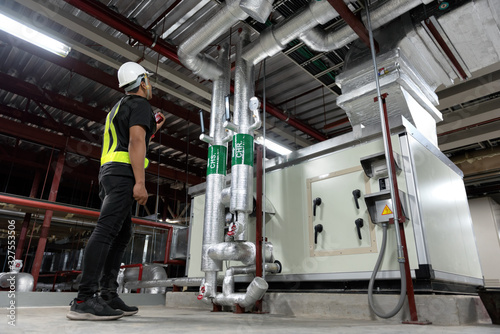Technician daily pressure check controls system for security functions in utility room at factory Canvas Print