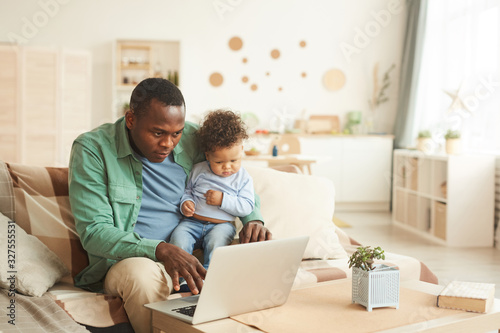 Portrait of mature African-American man working on laptop while babysitting son Canvas Print
