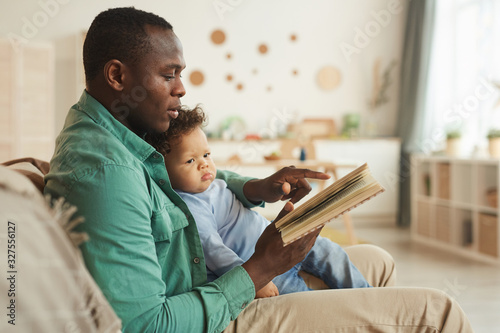 Fototapeta Side view portrait of caring African-American dad reading book to cute baby son