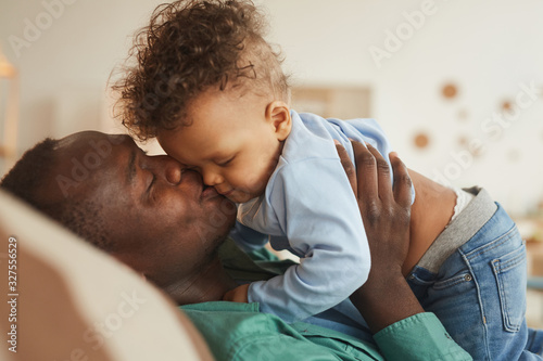 Photo Side view portrait of loving African-American dad kissing baby son while playing