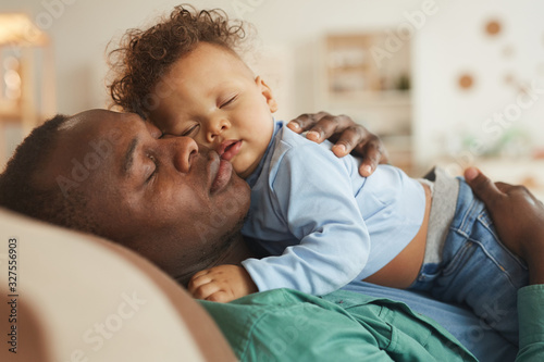 Side view portrait of loving African-American dad embracing baby son while playing at home, copy space