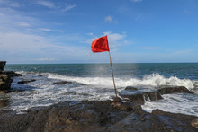 Red Flag On A Wooden Flagpole Flies On Coast Of Indian Ocean. Sign Warning Of Danger Of Big Breakers. Rock Cliff At Sacred Balinese Temple Tanah Lot. Waves Are Breaking On Rock Cliffs Of Black Lava.