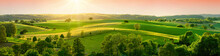 Panoramic Landscape With Beautiful Green Hills And Warm Sunshine Illuminating The Fields