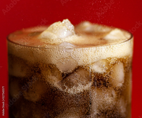 Close up of a cold, refreshing glass of cola with lots of ice and bubbles, on a deep red background Canvas-taulu