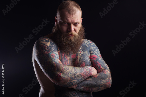 Tattooed brutal bearded man with a naked torso Tablou Canvas