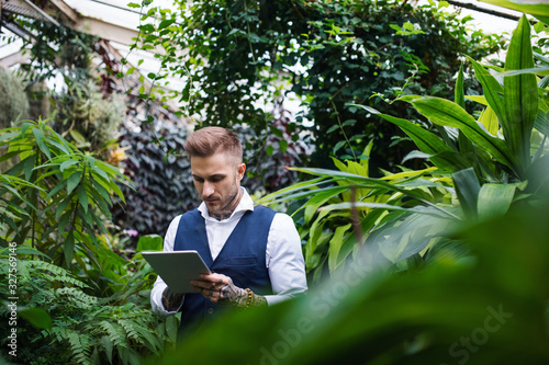 Young man with tablet standing in botanical garden, working.