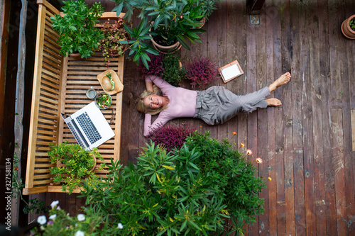 Fotografia Top view of senior woman with laptop lying outdoors on terrace, resting