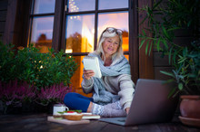 Senior Woman With Laptop Sitting Outdoors On Terrace, Working In The Evening.