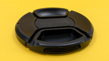 Camera Lens Cap On A Yellow Background