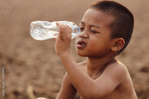 Fototapeta Asian boys are currently lacking clean water for consumption.