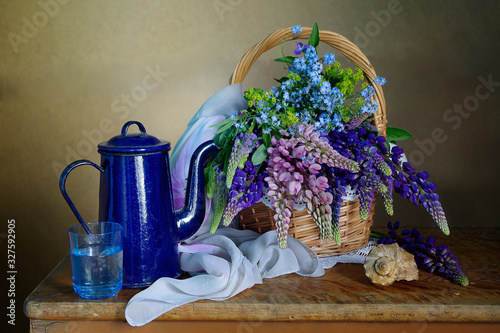 Fototapeta Still life with lupine flowers in a basket and a blue kettle on a table on a brown background obraz