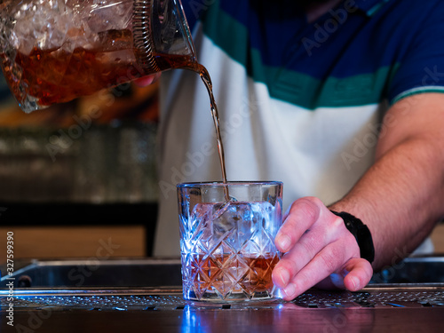 The bartender pours Negroni into a glass that he holds with his hand Canvas Print