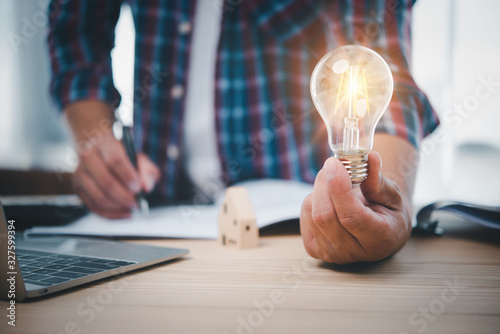 Fotografiet businessman hand holding lightbulb with office tools  on desk