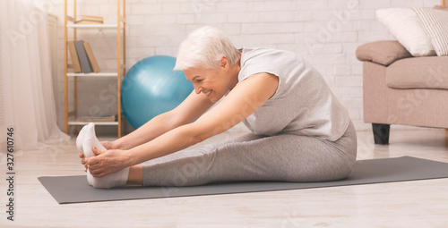 Active senior woman doing stretching exercises at home Fototapete