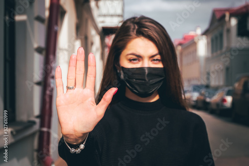 Girl, young woman in protective sterile medical mask on her face looking at camera outdoors, on asian street show palm, hand, stop no sign Canvas Print
