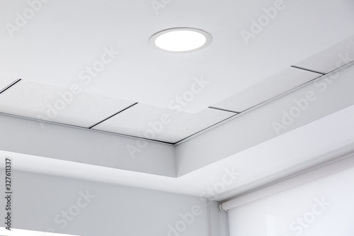 Photo multi-level ceiling with three-dimensional protrusions and a suspended tiled ceiling with a built-in round led light in the corner of the room, close up details